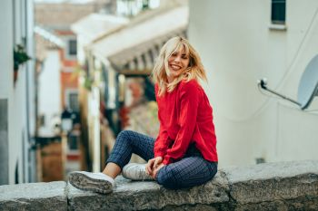 Happy young blond woman sitting on urban background moving her hair. Smiling blonde girl with red shirt enjoying life outdoors.
