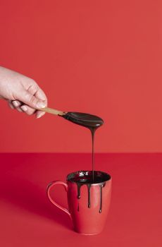Hand holding wooden spoon with dripping melted chocolate into red mug. Cup of chocolate glaze. Pouring melted chocolate. Christmas dessert decorating