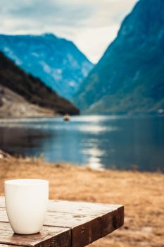 Mug on wooden table. Beautiful fjord norwegian scandinavian landscape in background, lake and mountains.. Mug on wooden table, fjord norwegian landscape