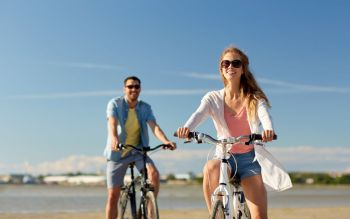 people, leisure and lifestyle concept - happy young couple riding bicycles on beach. happy young couple riding bicycles at seaside