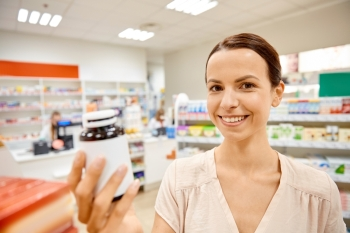 medicine, pharmaceutics, health care and customer concept - happy female customer with drug jar at pharmacy