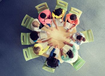 education, school, teamwork, gesture and people concept - group of international students with books sitting and pointing finger to center of table from top. group of international students pointing finger