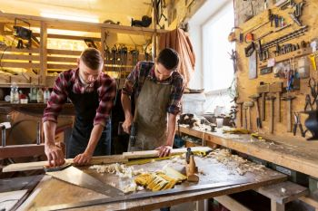 profession, carpentry, woodwork and people concept - two carpenters with wooden board, saw and electric drill working at workshop. carpenters working with wooden board at workshop