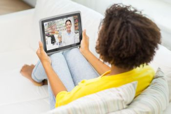 medicine, technology and healthcare concept - african american young woman having video chat with pharmacist on tablet pc computer at home. woman having video chat with pharmacist on tablet