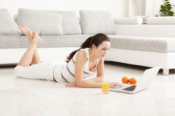 Beautiful Young Woman Surfing the Internet Online on Laptop, Orange Juice, Lying on the Floor in Living Room