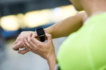 Young man using smartwatch at the gym. Caucasian male working out.