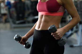 Young woman with beautiful abdomen lifting dumbells at gym. Girl wearing sportswear clothes.