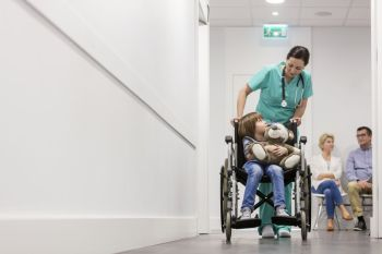 Nurse pushing boy with teddybear on wheelchair while patients waiting in hospital corridor