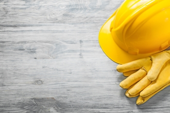Yellow hard hat protective gloves on wooden board copy space construction concept.