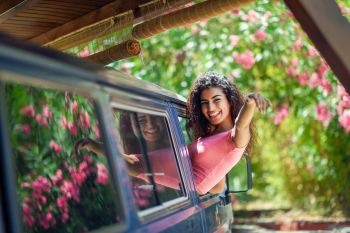 Happy young woman in a camper van enjoying spring time in a beautiful camping with pink flowers. Arab girl peeking out the window of a van