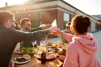 leisure and people concept - happy friends toasting drinks at rooftop party or picnic in summer. happy friends toasting drinks at rooftop party