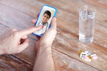medicine, technology and healthcare concept - close up of patient with pills and water on table having video chat with doctor on smartphone. patient having video chat with doctor on cellphone