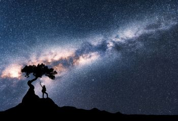 Milky Way and silhouette of woman under the tree growing from the rock on the mountain at night. Space background with starry sky, beautiful galaxy and girl. Scenery with Milky Way and people. Travel