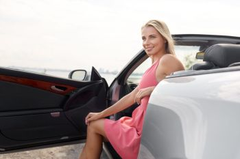 travel, road trip and people concept - happy young woman posing in convertible car at seaside. happy young woman posing in convertible car