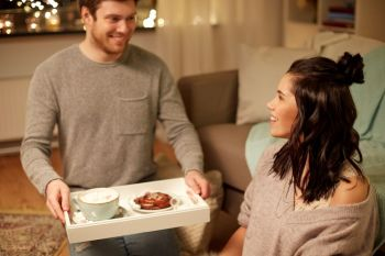 leisure, hygge and people concept - happy couple with food on tray at home. happy couple with food on tray at home
