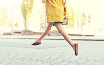 fashion and people concept - happy young woman or teenage girl legs flying above pavement on city street. young woman or teenage girl legs on city street