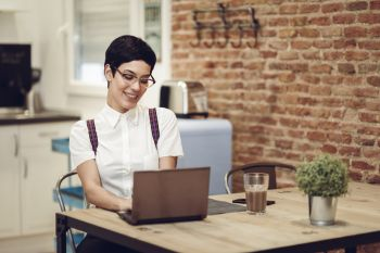 Spain, Madrid, Madrid. Young woman with very short haircut and eyeglasses typing with a laptop at home. Working at home concept.