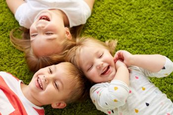 childhood, leisure and family concept - happy little kids lying on floor or carpet. happy little kids lying on floor or carpet