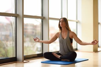 Young beautiful woman meditating in the lotus position in gym. Girl wearing sportswear clothes.