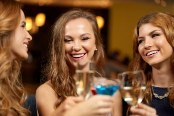 celebration, bachelorette party and holidays concept - happy women or female friends clinking glasses at night club. happy women clinking glasses at night club