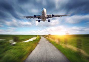 Aircraft and rural road with motion blur effect. Landscape with passenger airplane is flying over the asphalt road against cloudy sky, green grass field. Journey. Passenger airplane. Commercial plane