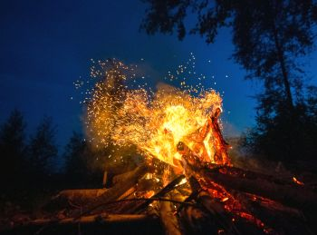Bright fire on a dark night in forest glade.. Bright fire on a dark night in a forest glade.