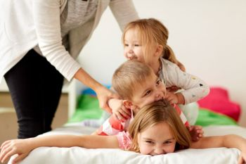 childhood, leisure and family concept - mother and happy little kids having fun at home. mother and happy little kids having fun at home