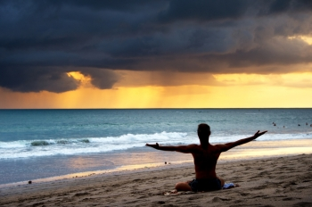 Silhouette of a man doing yoga exercise on the beach. Bali island, Indonesia