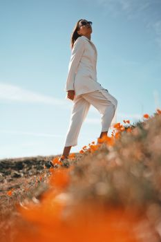 Outdoor lifestyle photo of beautiful young woman in white suit the poppy field. Freedom and independence
