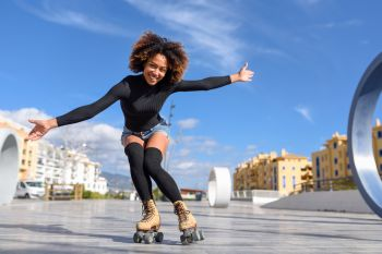 Black woman on roller skates riding outdoors on urban street. Young fit black woman on roller skates riding outdoors on urban street with open arms. Smiling girl with afro hairstyle rollerblading on sunny day