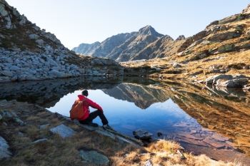 Male hiker takes a rest sitting next a mountain lake. Autumn sunny day. West italian Alps, Oropa, Piemonte, Italy, Europe.