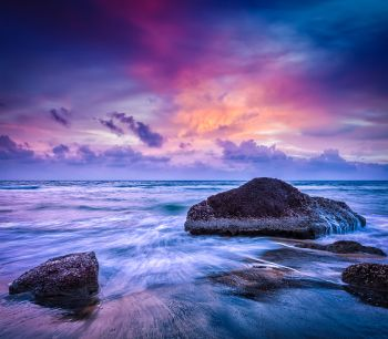 Tropical beach vacation background - waves and rocks on beach on sunset with beautiful cloudscape. Waves and rocks on beach of sunset