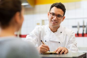 people, fast food and cooking concept - happy smiling chef at restaurant writing order and customer. chef at fast food restaurant writing order