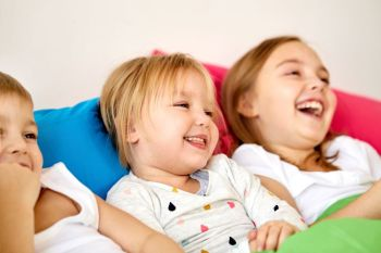 childhood, leisure and family concept - happy little kids having fun in bed at home. happy little kids having fun in bed at home