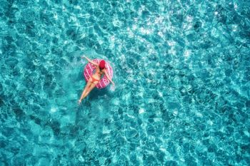 Aerial view of slim young woman swimming on the pink donut swim ring in clear blue sea at sunny bright day in summer. Tropical aerial landscape with girl, azure water. Top view from drone. Journey