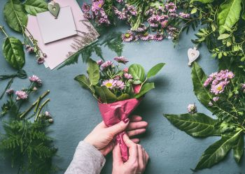 Female hands making lovely bouquet of pink flowers with  wrapping paper  on florist workspace, top view. Florist work, step by step