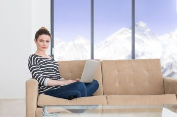 beautiful young woman on sofa at home websurfing  internet with laptop computer