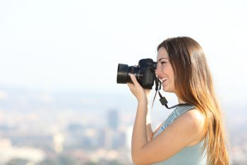 Side view portrait of a happy photographer taking photos with a dslr camera outdoors