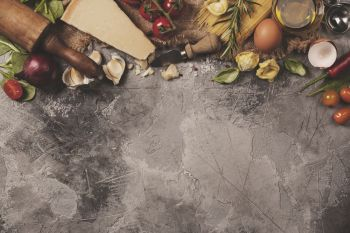 Italian food background with vine tomatoes, basil, spaghetti, spinach, onion, parmesan, olive oil, garlic, peppercorns, rosemary and eggs. Slate background