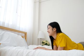 Young asian woman using laptop computer on bed in her bed room background with copy space, working at home, people and technology, lifestyles, education, business concept