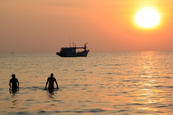 People, boat and sea with sunset in Thailand
