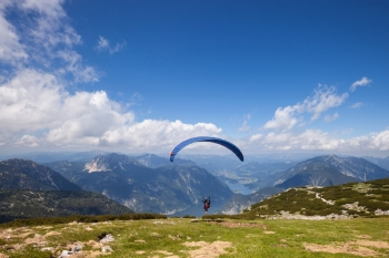 Parachute jumping extreme sport. Paraglider flying over mountains in summer day