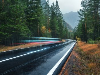 Blurred car on the road in spring forest in rain. Perfect asphalt mountain road in overcast rainy day. Roadway, pine trees in alps. Transportation. Highway in foggy woodland. Car in motion. Travel