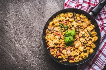 Tasty vegetarian tortellini pasta pot with vegetables sauce on rustic background , top view. Italian cuisine food concept