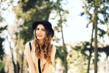 Happiness, consumerism, fashion and people concept - smiling young trendy hipster girl on city background in the sunlight outdoor
