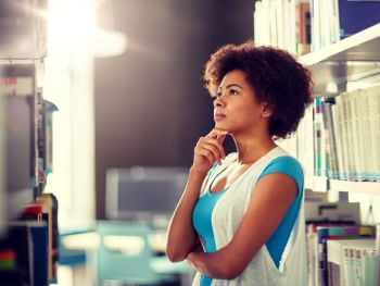 education, high school, university, learning and people concept - african american student girl choosing book at library. african student girl choosing book at library