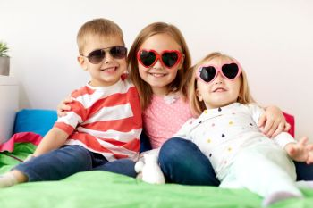 summer, valentines day and childhood concept - happy little kids in heart shaped sunglasses at home. happy little kids in sunglasses at home