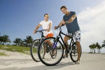 Portrait of two young men holding bicycles