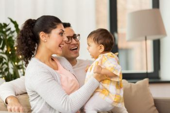 family, parenthood and people concept - happy mother, father with baby daughter at home. happy family with baby daughter at home
