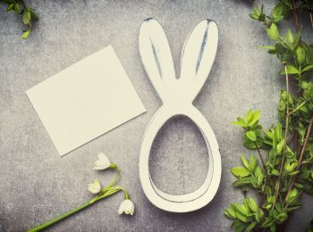 Easter greeting card with lily of the valley flowers, green brunches and bunny decor, top view